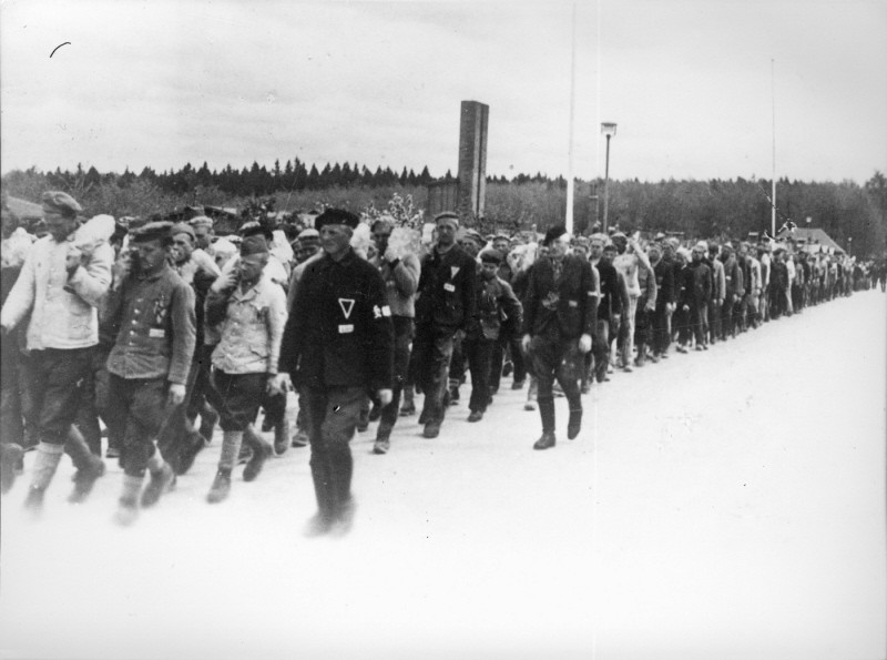 Returning from work in a stone quarry, forced laborers carry stones more than six miles to the Buchenwald concentration camp. [LCID: 19087]