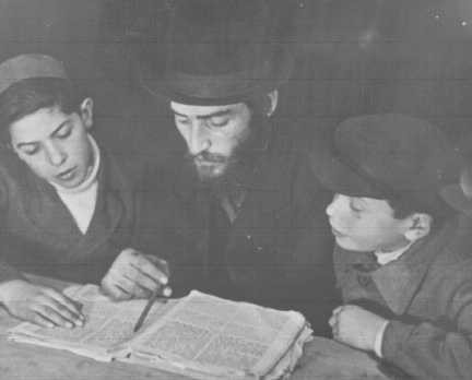 <p>A Jewish refugee teacher instructs children in religious law from the Talmud. Landsberg displaced persons camp, Germany, after 1945.</p>