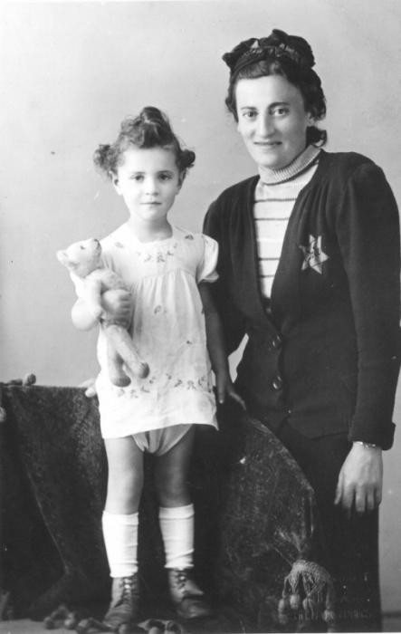 Helena Husserlova, wearing a Jewish badge, poses with her daughter Zdenka (holding a teddy bear) shortly before they were deported to Theresienstadt