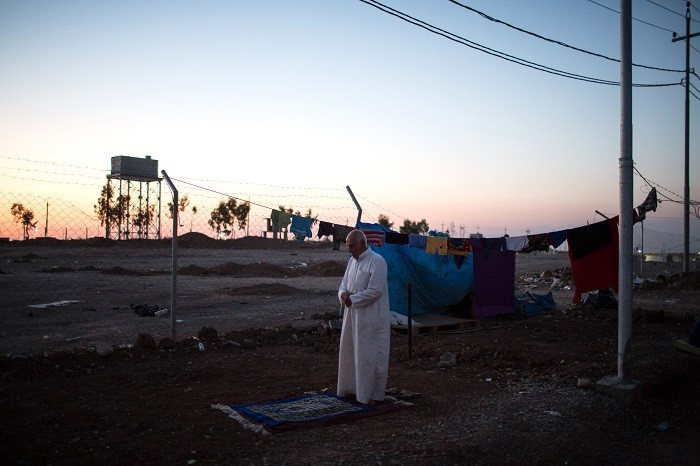 A Sunni man from Mosul, Iraq, prays as the sun sets over an internally displaced persons (IDP) camp near Erbil, Iraqi Kurdistan. [LCID: ref04]