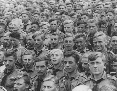 "Hitler Youth members listen to a speech by Adolf Hitler at a Nazi ""party day"" rally. [LCID: 85482]"