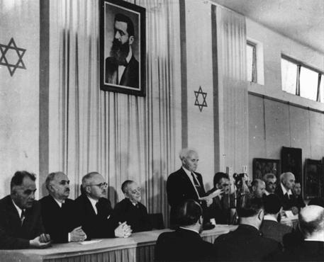 <p>Le Premier ministre David Ben-Gourion lit la Déclaration d'Indépendance de l'Etat d'Israël lors d'une cérémonie officielle à la suite de la partition de la Palestine par les Nations Unies. Tel-Aviv, 14 mai 1948.</p>