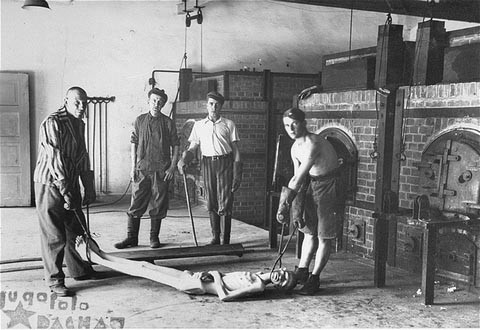Survivors of the Dachau concentration camp demonstrate the operation of the crematorium by preparing a corpse to be placed into one ... [LCID: 15028]