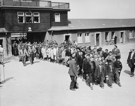 Escorted by American soldiers, child survivors of Buchenwald file out of the main gate of the camp. [LCID: 69158]
