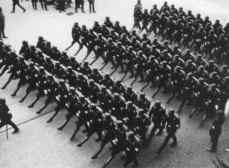 Members of the SS (Schutzstaffel; originally Hitler's bodyguard, later the elite guard of the Nazi state) parade during a rally. [LCID: 86520]