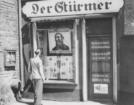 "<p>A young man looks at the antisemitic caricature in the display window of the Danzig office of ""Der Stürmer."" The poster reads: ""The Jews are our misfortune."" Danzig, 1939.</p>"