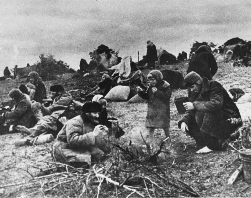 <p>Soviet refugees sit around a fire in a makeshift camp, following the German invasion of Soviet territory on June 22, 1941. Soviet Union, between 1941 and 1944.</p>