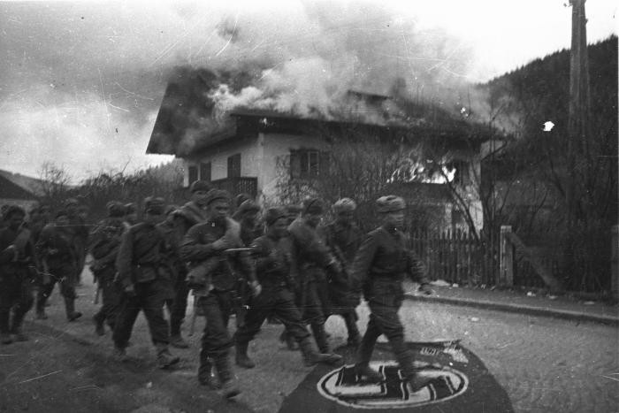 """<p><span style=""""font-weight: 400;"""">Soviet troops trample a Nazi flag as they march past a burning house on a street in the outskirts of Vienna. Photograph taken by Soviet photographer Yevgeny Khaldei. Vienna, Austria, April 1945.</span></p>"""