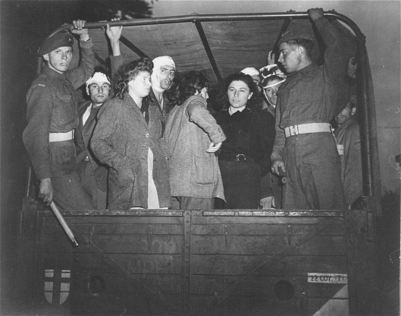 "<p>British soldiers guard Jewish refugees, forcibly removed from the refugee ship <a href=""/narrative/5265""><em>Exodus 1947</em></a>, on trucks leaving for Poppendorf <a href=""/narrative/6365"">displaced persons</a> camp. Photograph taken by Henry Ries. Kuecknitz, Germany, September 8, 1947.</p>"