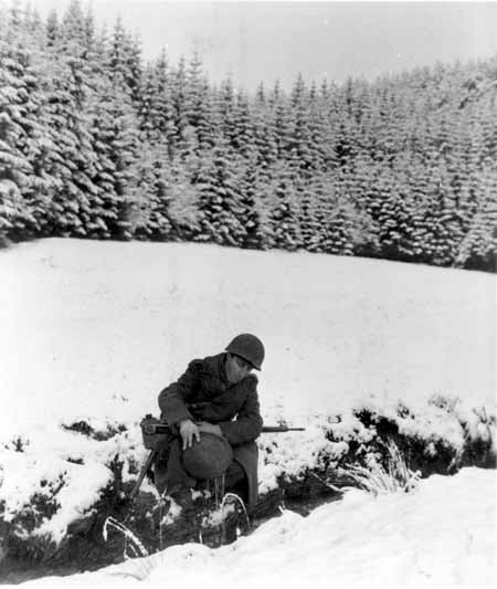 An American GI using his steel helmet to draw water from a stream during the Battle of the Bulge. December 22, 1944. US Army Signal Corps photograph taken by J Malan Heslop.