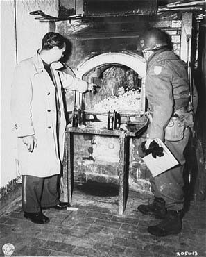 After the liberation of the Flossenbürg camp, a US Army officer (right) examines a crematorium oven in which Flossenbürg camp victims ... [LCID: 85707]