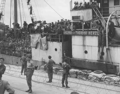"""<p>Des réfugiés à bord du """"Théodore Herzl"""", un bateau de l'Aliyah Beit (immigration clandestine), portent les corps (dans des linceuls blancs) de deux passagers tués lorsque le navire tentait de forcer le blocus britannique. Port de Haïfa, Palestine, 14 avril 1947.</p>"""