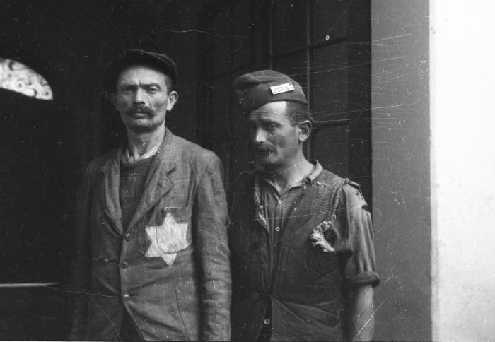 """<p><span style=""""font-weight: 400;"""">Portrait of two men standing in a doorway in the former Budapest ghetto, one of whom is wearing a painted yellow star on his jacket. Photograph taken by</span><span style=""""font-weight: 400;"""">Yevgeny Khaldei. Budapest, Hungary, 1945.</span></p>"""