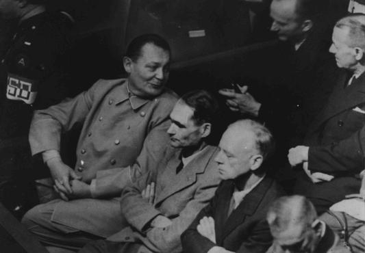 <p>Hermann Goering se tourne pour parler à Karl Doenitz lors du procès de Nuremberg. Rudolf Hess et Joachim von Ribbentrop sont assis à la gauche de Goering. Nuremberg, Allemagne, 26 novembre 1945.</p>