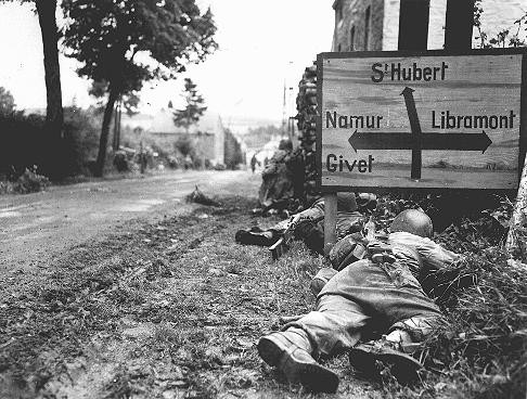 "<p>US soldiers of the <a href=""/narrative/7926/en"">8th Infantry</a> Regiment seek cover behind hedges and signs to return fire to German forces holding the town of Libin. <a href=""/narrative/5505/en"">Belgium</a>, September 7, 1944.</p>"