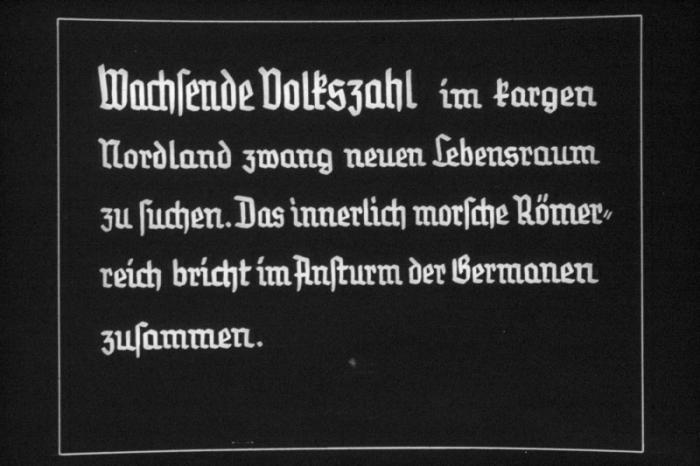 "<p>25th Nazi <a href=""/narrative/81/en"">propaganda</a> slide for a Hitler Youth educational presentation in the mid-1930s. The presentation was entitled ""5000 years of German Culture."" This slide references Lebensraum (the need for living space) in German history:  ""Wachsende Volkszahl im fargen Nordland zwang neuen Lebensraum zu suchen. Das innerlich morsche Römerreich bricht im Ansturm der Germanen zusammen."" Translated as:  ""Growing numbers of people in Nordland were forced to look for a new habitat. The inwardly crumbling Roman Empire collapses with the German onslaught.""</p>"