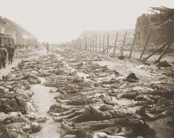 """<p>View of the main street of the Nordhausen concentration camp, outside of the central barracks (Boelke Kaserne), where the bodies of prisoners have been laid out in long rows. Nordhausen, Germany, April 13–14, 1945.</p> <p><span style=""""font-weight: 400;"""">This image is among the </span><a href=""""/narrative/8334/en""""><span style=""""font-weight: 400;"""">commonly reproduced and distributed</span></a><span style=""""font-weight: 400;"""">, and often extremely graphic, images of liberation. These photographs provided powerful documentation of the crimes of the Nazi era. </span></p>"""