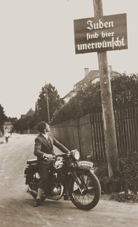 """A motorcyclist reads a sign stating """"Jews are not welcomed here."""" [LCID: 97470]"""