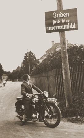 """<p>Мотоциклист читает вывеску с надписью: """"Евреи здесь нежелательны"""". Германия, прибл. 1935 год.</p>"""