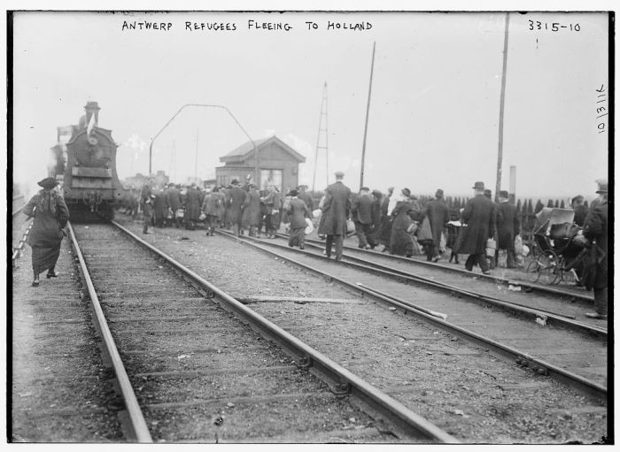 <p>Refugees from Antwerp, Belgium, walk along railroad tracks as they flee to the Netherlands during World War I. Belgium, 1914.</p>
