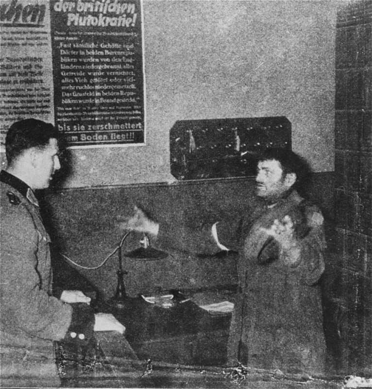 <p>A German policeman interrogates a Jewish man accused of trying to smuggle a loaf of bread into the Warsaw ghetto. Warsaw, Poland, 1942-1943.</p>