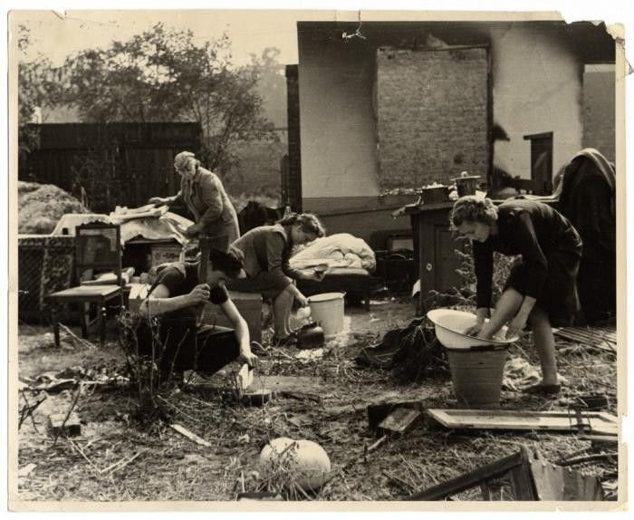 Members of a Polish family perform daily chores amidst the amidst the charred ruins of their home, destroyed during the German bombing of Warsaw. They have reassembled the remnants of their household furnishings outside. Photographed by Julien Bryan, circa 1939.