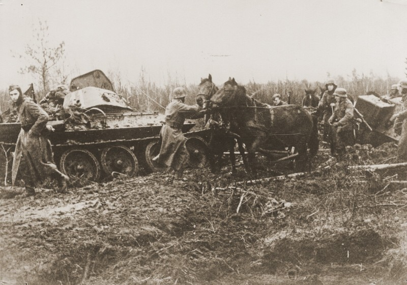 A German army column struggles through the mud, past a destroyed Soviet tank. [LCID: 09577]