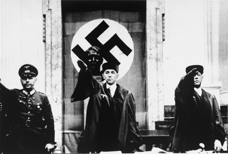 "<p>Roland Freisler (center), president of the Volk Court (People's Court), gives the Nazi salute at the trial of conspirators in the <a href=""/narrative/12002/en"">July 1944</a> plot to kill Hitler. Under Freisler's leadership, the court condemned thousands of Germans to death. Berlin, Germany, 1944.</p>"