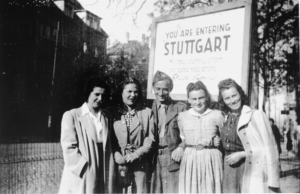 "<p>Henry Brauner (center) with his wife, Esther (second from right), pose with three friends in front of the entrance to the <a href=""/narrative/53598/en"">Stuttgart West</a> displaced persons (DP) camp, 1945.</p>"