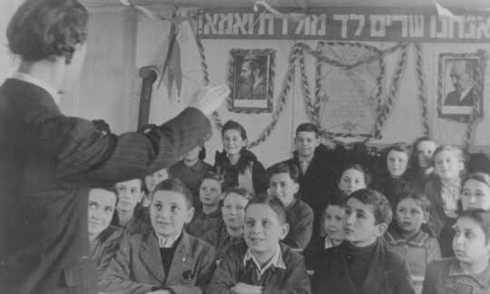 <p>Paroles de l'hymne national juif et portraits des dirigeants sionistes accrochés dans une classe. Camp de personnes déplacées de Feldafing, Allemagne, après avril 1945.</p>
