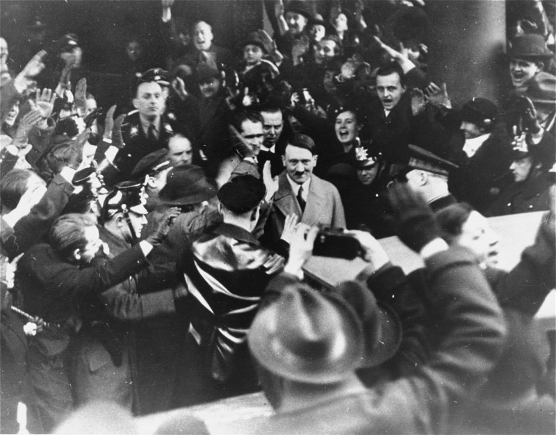 Germans cheer Adolf Hitler as he leaves the Hotel Kaiserhof just after being sworn in as chancellor. [LCID: 69710]