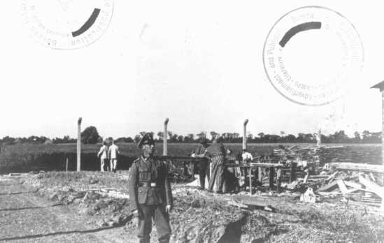 """<p>An SS guard watches <a href=""""/narrative/3384/en"""">prisoner laborers</a> at construction work. <a href=""""/narrative/6811/en"""">Neuengamme</a> concentration camp, Germany, wartime.</p>"""