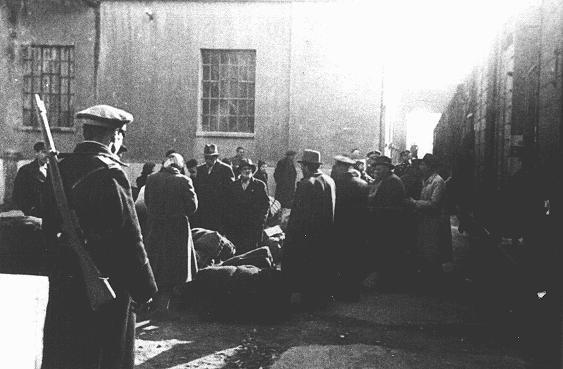 """<p>Judíos procedentes de Macedonia y Tracia, ocupadas por los búlgaros, durante su deportación a Lom desde la fábrica de tabaco """"Monopol"""" (que se usó como campo de tránsito). Estas personas fueron enviadas primero a Viena y luego al campo de Treblinka. Skopje, Yugoslavia, entre el 11 y el 31 de marzo de 1943.</p>"""