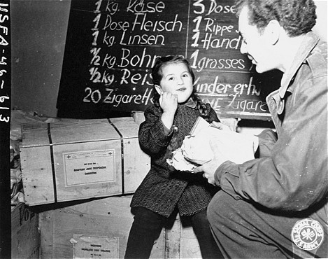 Harry Weinsaft of the American Jewish Joint Distribution Committee gives food to a Jewish refugee. [LCID: 46502]
