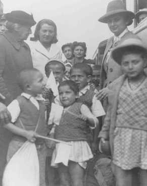 """<p>Henrietta Szold (left, in hat), founder of the Hadassah Women's Zionist Organization, welcomes some of the Polish Jewish refugee children known as the <a href=""""/narrative/11006/en"""">Tehran Children</a>, upon their arrival in Palestine. Atlit, Palestine, February 18, 1943.</p>"""