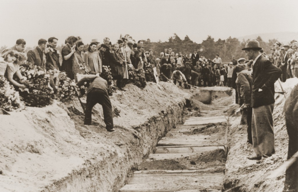 <p>Mourners and local residents shovel dirt into the mass grave of the victims of the Kielce pogrom during the public burial.</p>