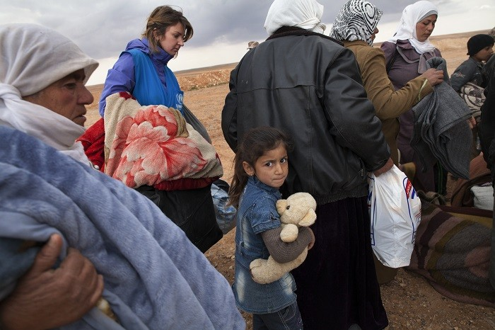 <p>Refugees displaced by the violence in Syria wait at a transit center in Jordan for trucks that will take them to the Zaatari refugee camp. February 2014.</p>