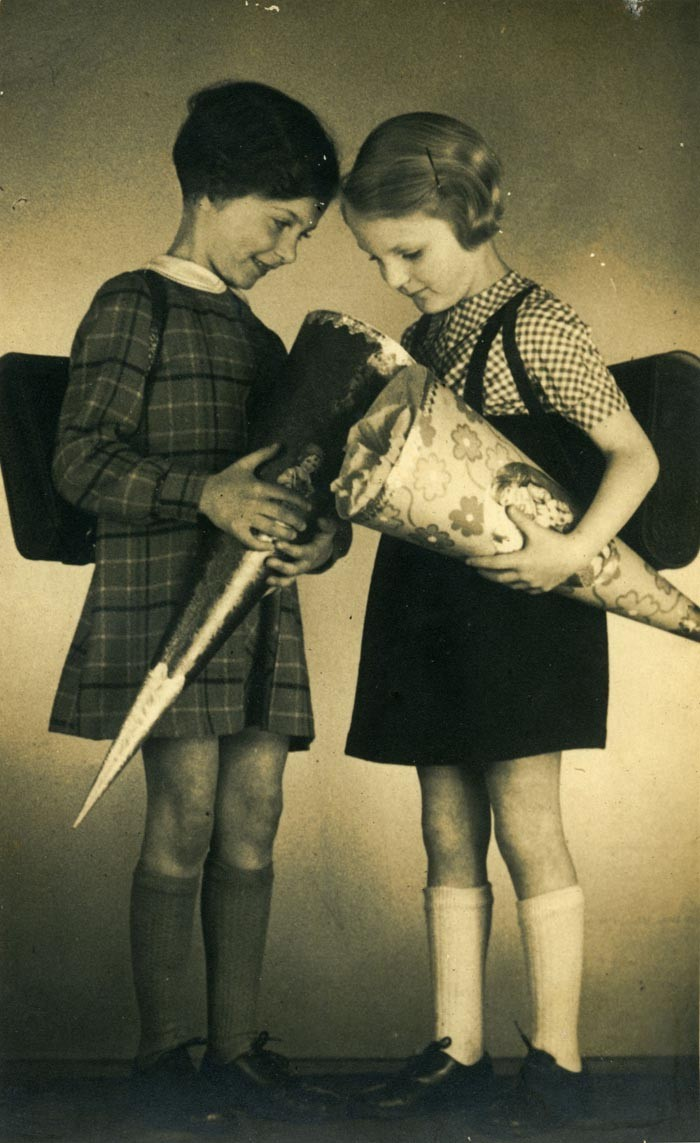 <p>Two Jewish girls (cousins Margot and Lotte Cassel) ready for their first day of school in Breslau, Germany, ca. 1937. As was traditional for all children in Germany, the cones were filled with treats to celebrate their first day of school.</p>