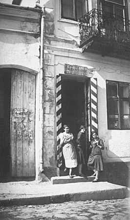 Malcia, Matla, and Rachel Saleschutz eat bagels in the doorway of their mother's store. [LCID: 67122]