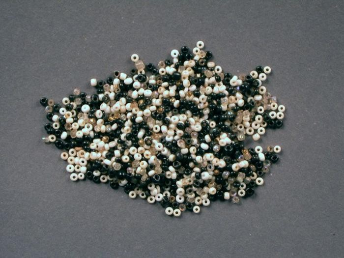"""<p>These tiny black, white, gold, and clear glass beads used by Rachel """"Chelly"""" de Groot from November 1942 to April 1944 and recovered by her brother Louis after the war. Chelly used the beads to make handicrafts.</p> <p>On November 16, 1942, Chelly, then 15, Louis, 13, and their parents Meijer and Sophia left Arnhem and went into hiding after the Dutch police warned them of a raid. Meijer and Sophia hid in Amsterdam while Chelly and Louis moved around to different locations. In summer or fall 1943, Chelly went to Amsterdam to live with her parents. In December, Louis was sent to Lemmer to live with the Onderweegs family.</p> <p>In February 1944, Dirk Onderweegs offered to take Chelly to a safer hiding place. But on April 8, 1944, four days<span class=""""morecontent"""">before Dirk was to return, Chelly and her parents were denounced and arrested. They were sent to <a href=""""/narrative/4469/en"""">Westerbork</a> transit camp, then to <a href=""""/narrative/3673/en"""">Auschwitz</a>. Chelly and Sophia were killed upon arrival in Auschwitz on May 22, 1944. Meijer was selected for a work detail and was killed later on September 30, 1944. </span></p> <p><span class=""""morecontent"""">Louis remained in hiding with the Onderweegs until liberation in mid-April 1945.</span></p>"""