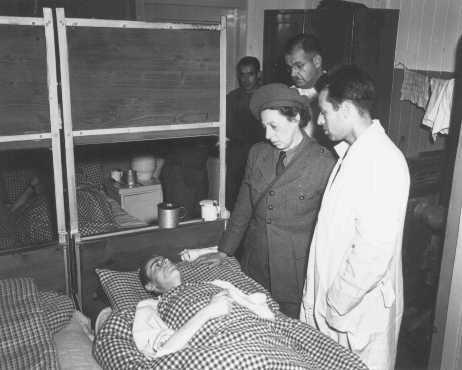 <p>Un employé de l'UNRRA (Administration des Nations Unies pour les secours et la reconstruction) avec un survivant du camp de concentration de Buchenwald après sa libération. Allemagne, 13 juin 1945.</p>