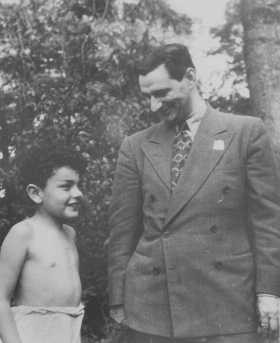 <p>Joseph Schwartz, director of the American Jewish Joint Distribution Committee in Europe, speaks with a Jewish child survivor during a relief mission to Poland, July 22, 1946.</p>
