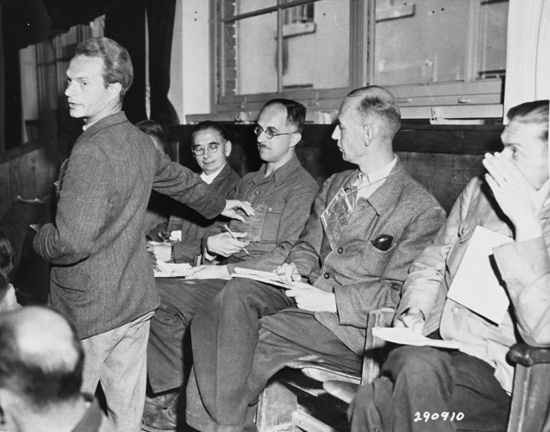 "<p>At an <a href=""/narrative/9935/en"">American military tribunal</a> held in Dachau, a witness for the prosecution identifies a doctor who had denied medical care to prisoners at the <a href=""/narrative/4909/en"">Dora-Mittelbau</a> concentration camp. Dachau, Germany, 1947.</p>"