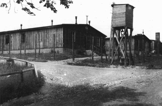 "<p>A watchtower and barracks at the <a href=""/narrative/7757/en"">Ohrdruf</a> subcamp of the <a href=""/narrative/3956/en"">Buchenwald</a> concentration camp. This photograph was taken after the US <a href=""/narrative/7807/en"">4th Armored Division</a> liberated the camp. Ohrdruf, Germany, June 1945.</p>"