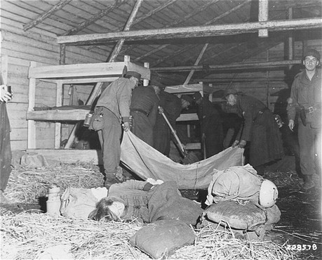 Medical corpsmen of the US 71st Infantry Division, 3rd US Army look on as captured German soldiers remove bodies from inside a barracks ... [LCID: 45036]