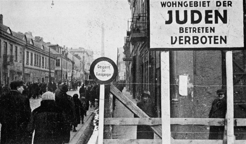 "<p>A German postcard showing the entrance to the <a href=""/narrative/2152"">Lodz</a> ghetto. The sign reads ""Jewish residential area—entry forbidden."" Signs forbidding entrance to Poles and Germans were posted at all entrances to the ghetto. Lodz, Poland, 1940–1941.</p>"