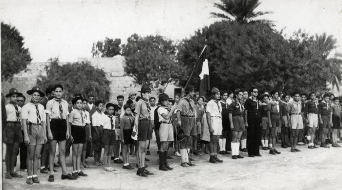 "<p class=""document-desc moreless"">Children stand at attention during a flag raising ceremony at the Ayindram Betar summer camp. Tunisia, North Africa, 1946. </p>