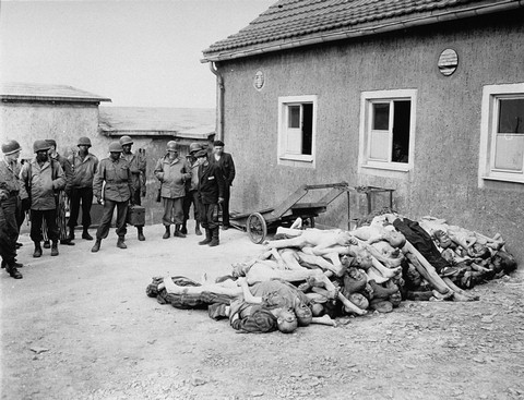 <p>American troops, including African American soldiers from the Headquarters and Service Company of the 183rd Engineer Combat Battalion, 8th Corps, US 3rd Army, view corpses stacked behind the crematorium during an inspection tour of the Buchenwald concentration camp. Among those pictured is Leon Bass (the soldier third from left). Buchenwald, Germany, April 17, 1945.</p>