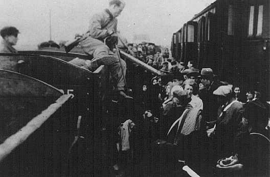 <p>Les Juifs du ghetto de Lodz sont contraints de passer par une voie ferrée étroite à Kolo lors de leur déportation vers le camp d'extermination de Chelmno. Kolo, Pologne, probablement en 1942.</p>