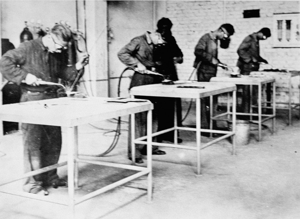 """<p>Forced labor in a workshop in the Monowitz camp, part of the <a href=""""/narrative/3673/en"""">Auschwitz camp complex</a>. Poland, between 1941 and January 1945.</p>"""